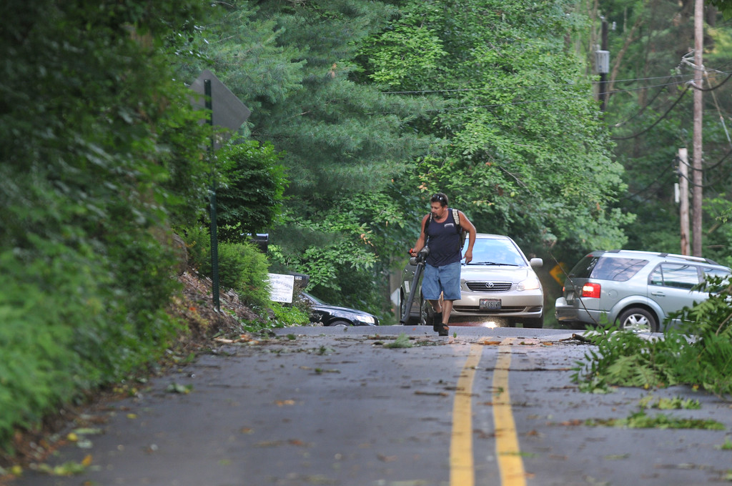 Description of . A man uses a power blower to clean debris from Roberts Road as rush hour traffic turns around in Radnor Wednesday morning. Photo Pete Bannan