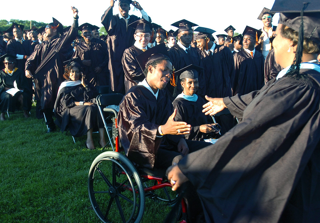 Description of . Calvin Jones receives a hand shake during commencement for Chester High School at the athletic field, Friday. (Times Staff / JULIA WILKINSON )