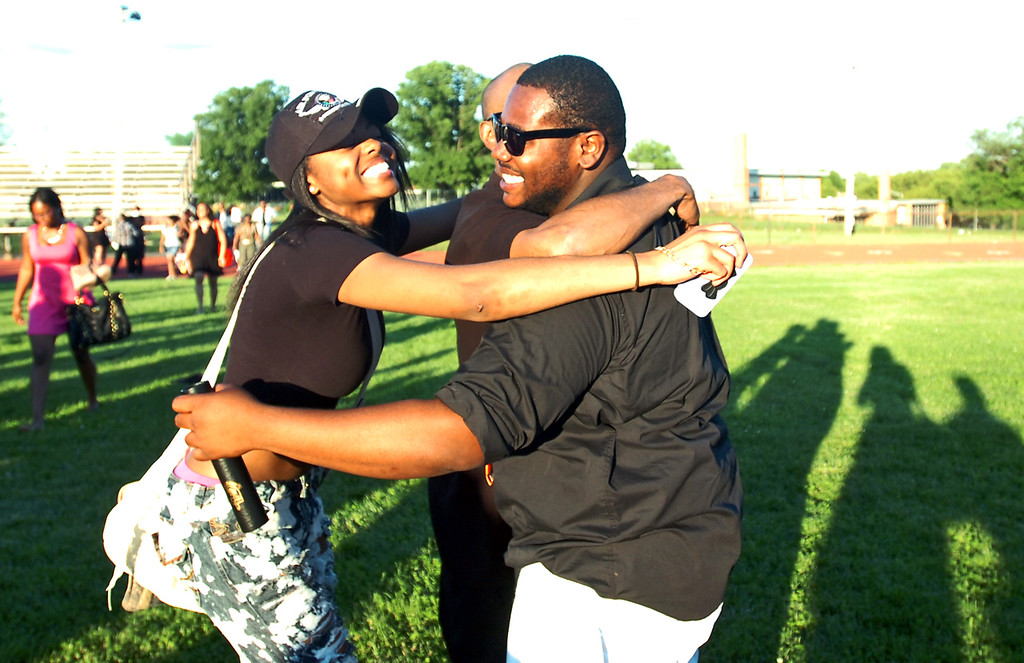 Description of . Berniece Johnson joins dad Brian Johnson to congratulate brother, also Brian Johnson in a family hug after commencement, Friday. (Times Staff / JULIA WILKINSON )