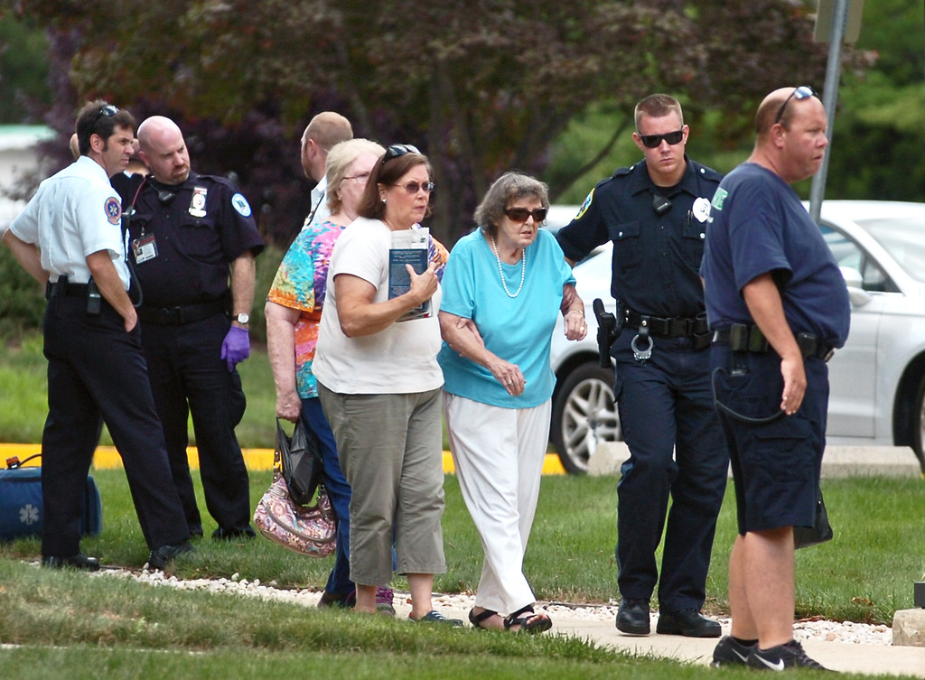 Description of . Police evacuate people from the Sister Marie Lenahan Wellness Center on the campus of Mercy Fitzgerald Hospital after a shooting Thursday. (Times Staff / JULIA WILKINSON )