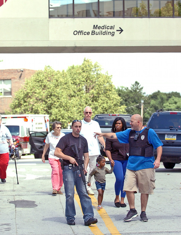 Description of . Police evacuate people from the Sister Marie Lenahan Wellness Center in Yeadon on the campus of Mercy Fitzgerald Hospital after a shooting Thursday. (Times Staff / JULIA WILKINSON )